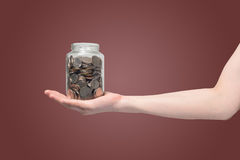 Hand hold piggy bank with bath coins on isolated gradient red background. Royalty Free Stock Image