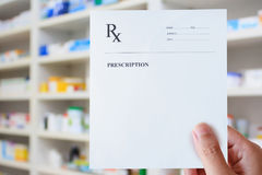 Hand hold prescription paper over the pharmacy Stock Image