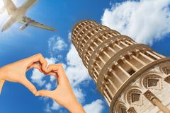 Hand hold red heart over Pisa tower and airplane. Red love heart and on background Pisa tower, airplane with tourists passing by royalty free stock photo