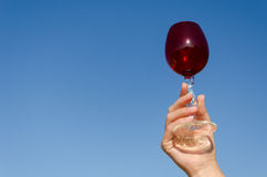 Hand hold red wineglass squirm stem on blue sky. Female hand hold red clear wineglass with squirm stem on blue sky background Stock Photography