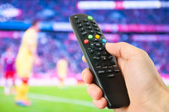 Hand hold remote control in front of tv. Closeup stock photography