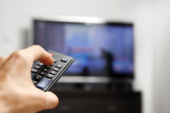 Hand Hold Remote Control In Front Of Tv Stock Image