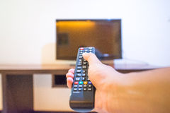 Hand hold remote for control television (Shallow Blurred) Royalty Free Stock Photography