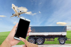 hand hold smart phone with airplane in the sky and Truck for tra Royalty Free Stock Images