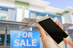 Hand hold smart phone on blurred new house. For sale Stock Image