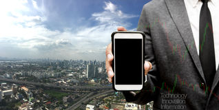 Hand hold smart phone with city in background Stock Image