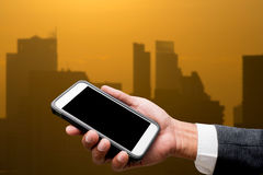Hand hold smart phone with city light in background. Hand hold smart phone with city lights in background Royalty Free Stock Image