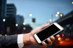 Hand hold smart phone with city light in background. Hand hold smart phone with city lights in background Stock Image