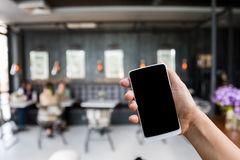 Hand hold smart phone,mobile over blurred image of coffee shop. Restaurant:concept learning or search Stock Photo