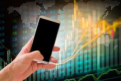 Hand hold smart phone on stock market indicator and financial da Stock Image
