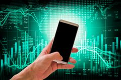 Hand hold smart phone on stock market indicator and financial da Stock Photos