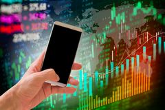 Hand hold smart phone on stock market indicator and financial da. Ta background for your design. Double exposure financial graph and stock indicator. Abstract Royalty Free Stock Photography