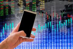 Hand hold smart phone on stock market indicator and financial da. Ta background for your design. Double exposure financial graph and stock indicator. Abstract Royalty Free Stock Photos