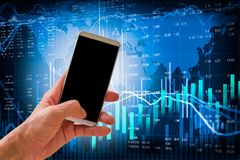 Hand hold smart phone on stock market indicator and financial da. Ta background for your design. Double exposure financial graph and stock indicator. Abstract Stock Photography