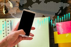 Hand hold smart phone on stock market indicator and financial da. Ta background for your design. Double exposure financial graph and stock indicator. Abstract Stock Images