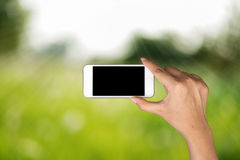 Hand hold and smart phone, tablet,cellphone on day light with gr Stock Image