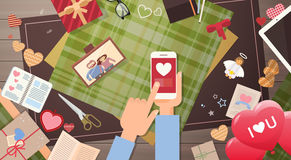 Hand Hold Smart Phone Valentine Day Gift Card Holiday Decorated Workspace Desk Top Angle View Stock Images