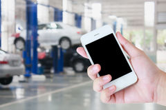 Hand hold smartphone with auto tire repair services Stock Photos