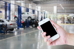 Hand hold smartphone with auto tire repair services. Blurred background Royalty Free Stock Photos