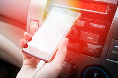 Hand hold smartphone in car,Charger plug phone on car Royalty Free Stock Photo
