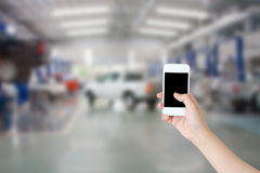 Hand hold smartphone with car repair service center Stock Photography