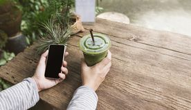 Hand hold smartphone or mobile phone and glass of green tea. In garden nature green background Royalty Free Stock Images