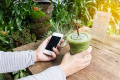 Hand hold smartphone or mobile phone and green tea. Hand hold smartphone or mobile phone and glass of green tea in garden nature green background Royalty Free Stock Photo