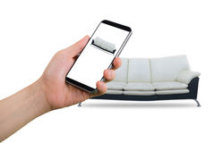 Hand hold smartphone, tablet, cell phone with blank screen on blurry modern black and white sofa, Online shopping decoration conc Stock Photo