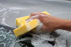 Hand hold sponge over the car for washing. Stock Images