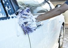 Hand hold sponge over the car for washing Royalty Free Stock Photography
