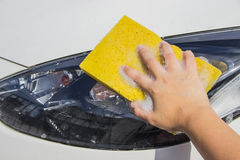 Hand hold sponge over the car for washing. Car Hand Wash with Yellow Sponge and Soap on a white car Royalty Free Stock Photo