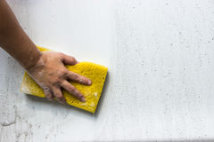 Hand hold sponge over the car for washing. Car Hand Wash with Yellow Sponge and Soap on a white car Royalty Free Stock Images