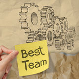 Hand hold sticky note with best team word with  gear Stock Image