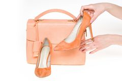 Hand hold stilettos at female bag isolated on white background. Shoes on high heels and handbag of coral color, leather material. Fashion, style, accessory stock photos