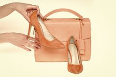 Hand hold stilettos at female bag on white background. Shoes on high heels and handbag of coral color, leather material. Fashion, style, accessory. Presenting royalty free stock photography