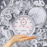 Hand hold stopwatch with figures and gears Stock Photo