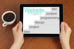 Hand hold tablet pc with website project's development steps Royalty Free Stock Photos