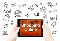 Hand hold tablet with Shopping Online word on screen with doodle Stock Image