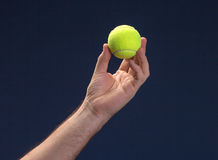 Hand hold Tennis ball. On blue background Royalty Free Stock Images