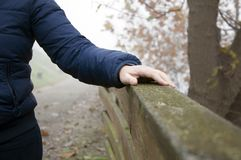 Hand hold on to the old wooden handrail. Female hand hold on to the old wooden handrail stock photos