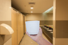 Hand hold toilet paper. On toilet background Royalty Free Stock Photos