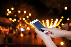 Hand hold and touch screen smart phone, on abstract  blurred pho Stock Image