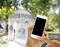 Hand hold and touch screen smart phone on wedding tent blurred b Royalty Free Stock Images