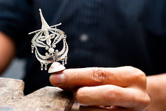 Hand Hold traditional Wau Bulan Silver Filligr. Crafter Hand Holding a traditional Wau Bulan Kite Silver Filligree Royalty Free Stock Photos