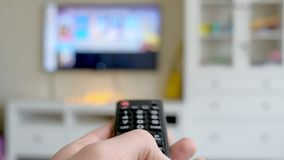 Hand hold TV remote control. TV on the background. 4k stock video