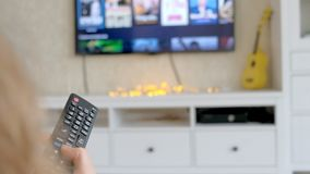 Hand hold TV remote control. TV on the background. 4k stock video footage
