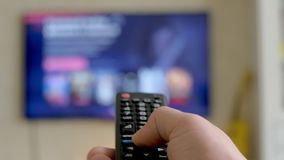 Hand hold TV remote control. TV on the background. 4k stock footage
