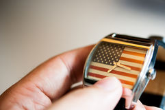 Hand hold a watch America flag in background watch. Focus on America flag in background watch, fashion watch 4th July, God Bless America, America flag Royalty Free Stock Photo