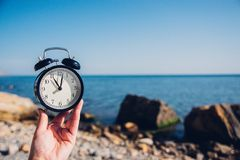 Free Hand Hold Watch On Beach Background.Alarm Clock On Sea And Sand Background Different Time With Summer Vacation.Vacation Time Conce Royalty Free Stock Images - 118838669