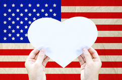 Hand hold white heart paper on United States of America flag Stock Photography